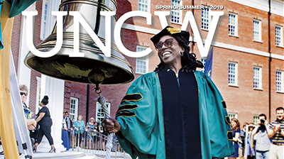 UNCW magazine cover with graduate ringing bell