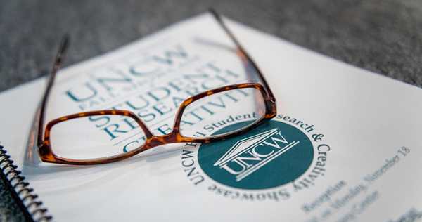 pair of glasses resting on a student research book